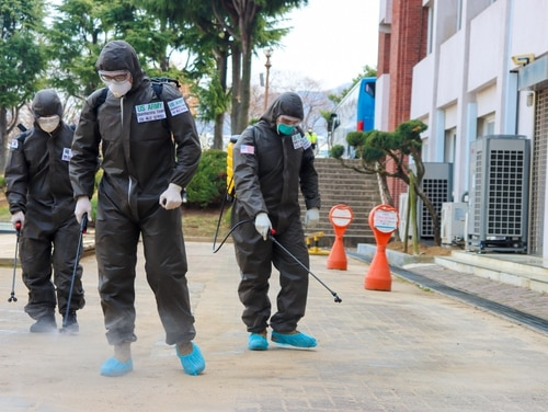 Two U.S. soldiers and a Republic of Korea soldier spray a COVID-19 infected area with a solution of disinfectant in Daegu, Republic of Korea, March 13, 2020. (Spc. Hayden Hallman/Army)
