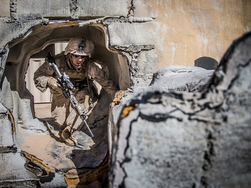 Sgt. Dalyss Reed, a rifleman with Kilo Company, Battalion Landing Team 3rd Battalion, 5th Marine Regiment, 11th Marine Expeditionary Unit, maneuvers through a breach hole while conducting an urban platoon assault. (Lance Cpl. Dalton S. Swanbeck/Marine Corps)