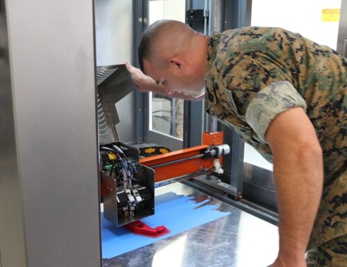 Gunnery Sgt. Doug McCue, a machinist with the 2nd Maintenance Battalion at Camp Lejeune, North Carolina, demonstrates the capabilities of a large-build 3-D printer in the X-FAB Facility Aug. 1. (Kaitlin Kelly/U.S. Marine Corps)