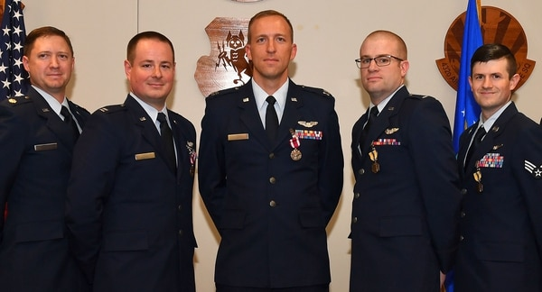From left, four MQ-9 Reaper pilots with the 432nd Air Expeditionary Wing — retired Maj. Asa, Capt. Evan, Capt. Abrham and 1st Lt. Eric — and Senior Airman Jason, a sensor operator, received medals with