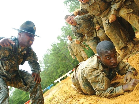 Drill Sgt. Primus Brown instructs infantry trainees as they learn to high-crawl through a sand pit as part of an obstacle course on Fort Benning's Sand Hill. (David Dismukes/Army)