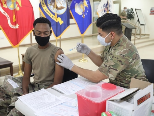Spc. Michael Meza of the 228th Combat Support Hospital, administers the Moderna COVID-19 vaccine to Spc. Sarrod Hearn, a radiology specialist, at Camp Arifjan, Kuwait, on Jan. 18. (Army)