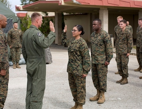 Lance Cpl. Remedios Cruz, Marine Aircraft Group 12, recites the Oath of Enlistment after being meritoriously promoted at Anderson AFB, Guam, 4 Dec. 2013. Now she's facing separation for fraternizing in an infantry unit.(Lance Cpl. Richard Currier/Marine Corps)