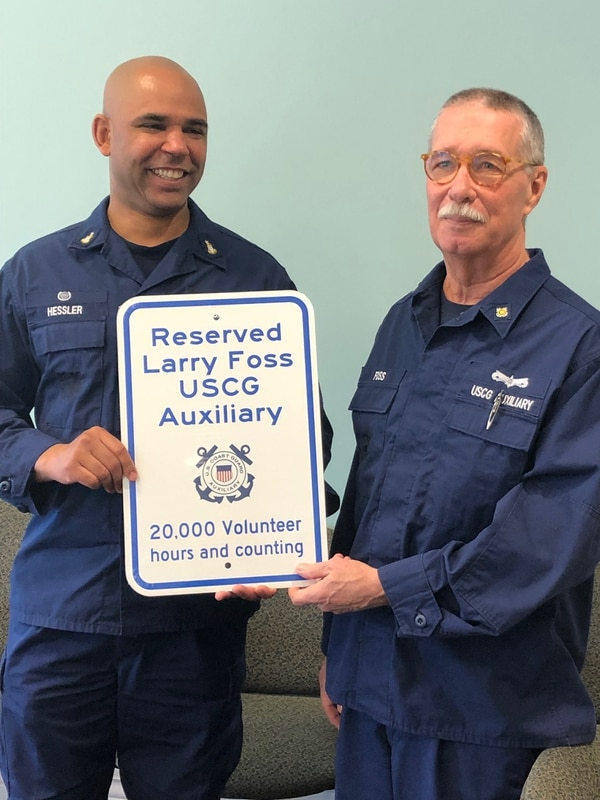 Senior Chief Petty Officer Carlos Hessler (left), officer in charge of Coast Guard Station Chatham, on Dec. 18 displays a sign that will reserve a special parking space at the facility for long-serving Auxiliarist Larry Foss. Foss was honored for contributing more than 20,000 hours of volunteer service over the past 17 years. (Coast Guard)