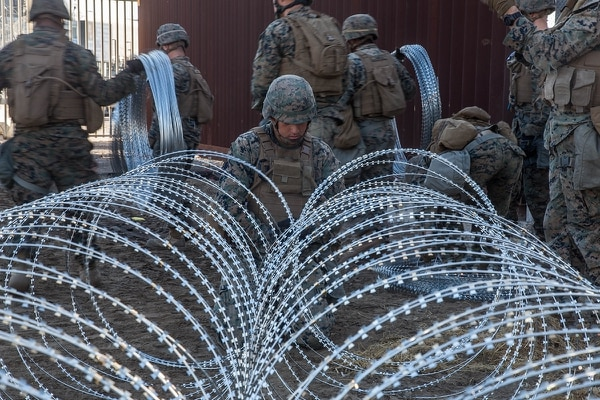 Marine Corps Lance Cpl. Martin Velasco, a combat engineer with 7th Engineer Support Battalion, Special Purpose Marine-Air Ground Task Force 7, ties concertina wire while participating in border support near the San Ysidro Port of Entry in California, Nov. 25, 2018. (Staff Sgt. Rubin J. Tan/Marine Corps)
