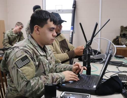 A soldier with the 1-508th Parachute Infantry Regiment (PIR), 82nd Airborne Division (Air Assault) configures a leader radio as part of a live fires exercise at Camp Atterbury, Indiana in January, 2019. The radio is one component of the Integrated Tactical Network kit and is used to transmit position location information on either the secure but unclassified TSM commercial waveform or SECRET SINCGARS waveform. Photo Credit: (Justin Eimers/Army PEO C3T)