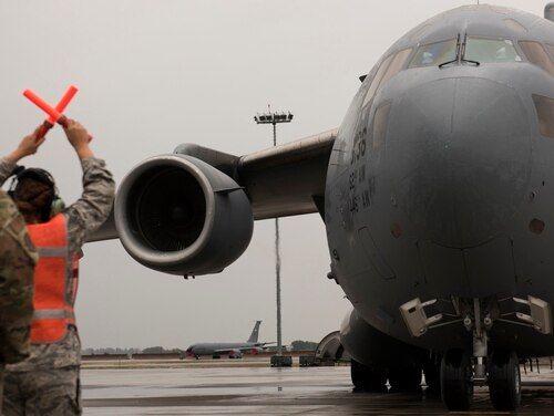 Senior Airman Ciana Jones, 62nd Maintenance Squadron crew chief, directs a C-17 Globemaster to a parking spot at the start of Air Mobility Command's Mobility Guardian 2019 exercise at Fairchild Air Force Base, Washington, Sept. 8. (SrA Ryan Lackey/Air Force)