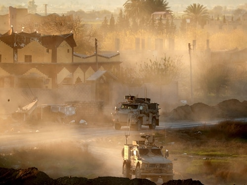 U.S. Army vehicles drive in support of Syrian Democratic Forces near Hajin, in Deir Ezzor province, eastern Syria, on Dec. 15, 2018. (Delil Souleiman/AFP via Getty Images)