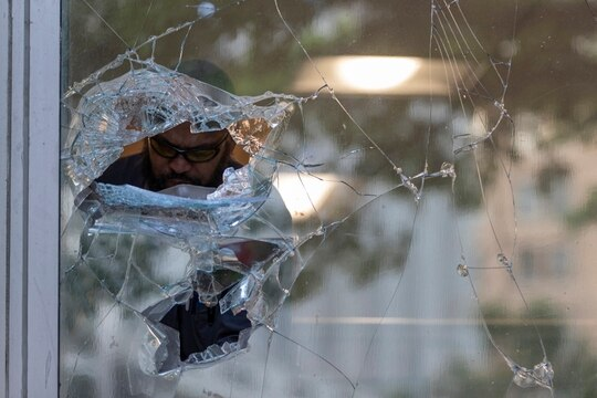 A man is seen through a shattered window at the Department of Veterans Affairs as he cleans up glass in Washington, Monday, June 1, 2020, after a night of protests over the death of George Floyd. Prosecutors say Floyd was murdered by a Minneapolis police officer after being restrained. (Carolyn Kaster/AP)