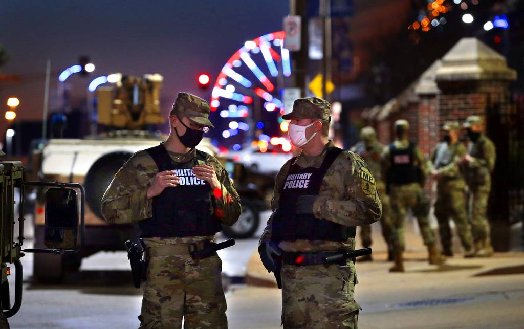 Members of the Missouri National Guard stand near the entry to the St. Louis City Hall parking lot Tuesday, Nov. 3, 2020, as Election Day comes to a close.