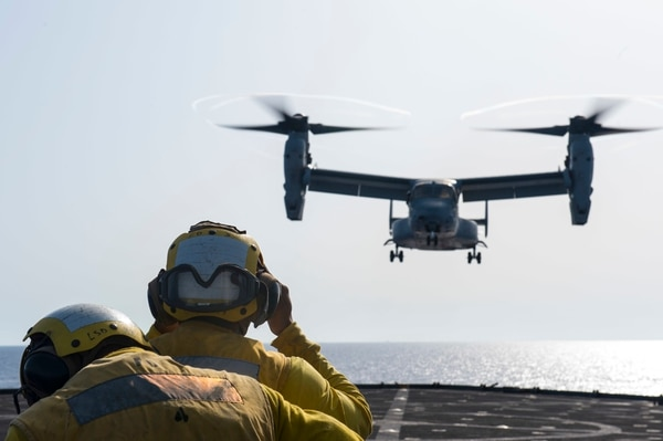 Boatswain's Mate 3rd Class Zachary Holcomb signals an MV-22 Osprey to land on the flight deck of the dock landing ship Fort McHenry (LSD 43) during flight operations. (Mass Communication Specialist 3rd Class Adam Austin/Navy)