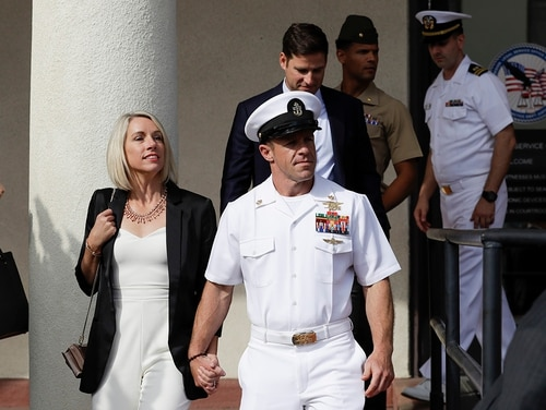 "Special Warfare Operator Chief Edward ""Eddie"" Gallagher, center, walks with his wife, Andrea, as they leave a military court on Naval Base San Diego on July 2. (Gregory Bull/AP)"