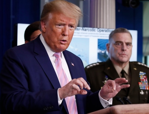 President Donald Trump speaks on April 1 from the White House, as Chairman of the Joint Chiefs Gen. Mark Milley, listens. (Alex Brandon/AP)