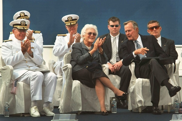 President George H.W. Bush and former first lady Barbara Bush join Adm. Vern Clark, chief of naval operations, on Aug. 26, 2003, as they watch the Navy's parachute team The Leapfrogs perform during a keel laying ceremony for the aircraft carrier George H.W. Bush. (Chief Photographer's Mate Johnny Bivera)