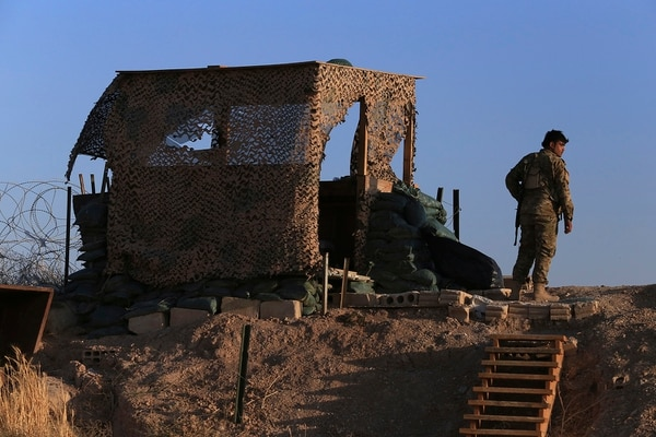 A fighter from the Syrian Democratic Forces, SDF, stands inside a post where U.S. troops were based, in Tel Abyad town, at the Syrian-Turkish border, Syria, Monday, Oct. 7, 2019. (Ahmad Baderkhan/AP)