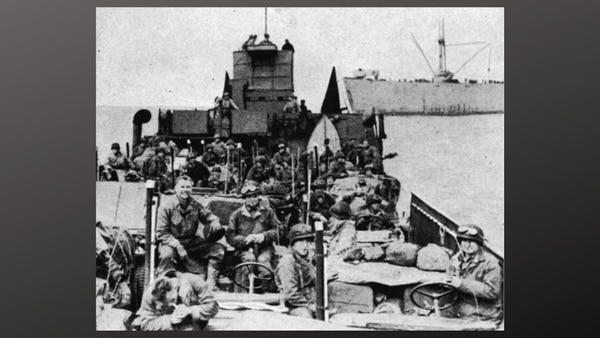 B Battery, 321st Glider Artillery Battalion on their landing craft after disembarking from the SS John S. Mosby, background. Pfc. Elmo Smiley is seen smiling and wearing goggles on his helmet, at right front, before the vessel was strafed by the Luftwaffe and shelled by friendly fire. Pfc. Lawrence Boudreaux was one of the 15 men injured, June 9, 1944.