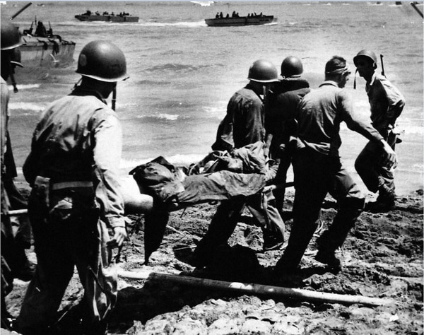U.S. Coast Guardsmen from an invasion transport remove an Army casualty from the flaming beach on Leyte Island as the weight of liberation strikes into the heart of the Philippines, 20 October 1944. (National Archives)