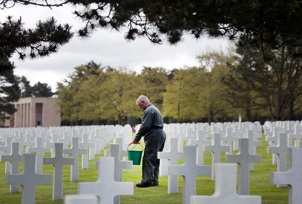 In this May 2, 2019, photo, a worker cleans moss off the headstones of World War II soldiers at the Normandy American Cemetery in Colleville-sur-Mer, France. The beauty of the cemetery strikes any visitor entering the site, with its immaculate lawns, majestic pines, commanding view of the Atlantic and row upon row of crosses. (Virginia Mayo/AP)