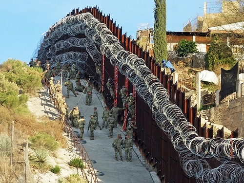 In this Feb. 2, 2019, photo, U.S. Army troops place additional concertina wire to the border fence on a hillside above Nelson Street in downtown Nogales, Ariz. Nogales, Mexico is seen at right. The small Arizona border city is fighting back against the installation of razor fencing that now covers the entirety of a tall border fence along the city's downtown area. The city of Nogales, which sits on the border with Nogales, Mexico, is contemplating a proclamation Wednesday, Feb. 6, 2019, condemning the use of concertina wire in its town. (Jonathan Clark/Nogales International via AP)