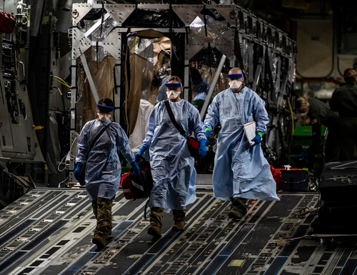 Three U.S. Air Force medical airmen exit a C-17 Globemaster III aircraft following the first-ever operational use of the Transport Isolation System at Ramstein Air Base, Germany, April 10, 2020. (Staff Sgt. Devin Nothstine/Air Force)