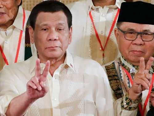 In this Feb. 22 photo, Philippine President Rodrigo Duterte, left, and Moro Islamic Liberation Front chairman Murad Ebrahim, right, flash peace signs following oath-taking ceremony for the creation of the Bangsamoro Transition Authority at the Presidential Palace in Manila, Philippines. (Bullit Marquez/AP)