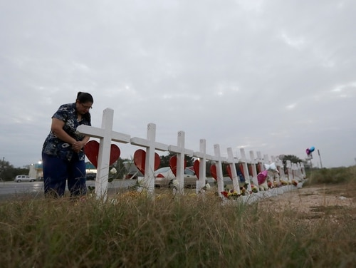 A woman visits a makeshift memorial for the victims of former airman Devin Kelley, who gunned down 26 people at a Texas church in November. Kelley had been convicted of assaulting his wife and child, but civilian authorities were not properly notified of the crime and he was able to purchase firearms. (Eric Gay/AP)