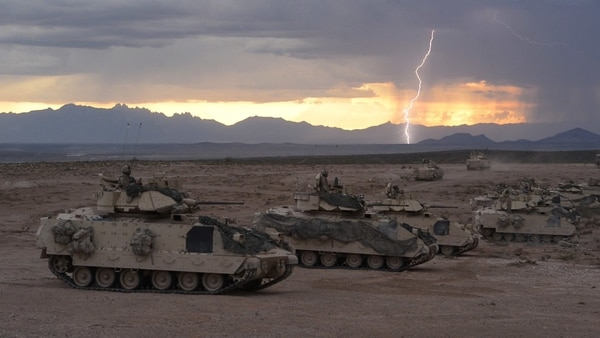 Lightning strikes as Bradley Fighting Vehicles from the 30th Armored Brigade Combat Team prepare to fire TOW missiles during an exercise at Fort Bliss, Texas, Aug. 16, 2018. (Staff Sgt. Brendan Stephens/Army)