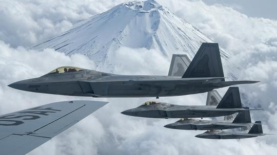 Four F-22 Raptors fly alongside a U.S. Air Force KC-135 Stratotanker during fifth-generation fighter training near Mount Fuji, Japan, April 1, 2021. (Senior Airman Rebeckah Medeiros/Air Force)