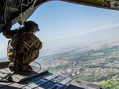 A flight engineer scans the outlying neighborhoods of Jalalabad, Afghanistan, while crouched on the rear door of a CH-47 Chinook helicopter. A House panel approved plans for a $716 billion defense authorization plan for fiscal 2019 early on Thursday morning. (Sgt. 1st Class Randall Pike/Army)