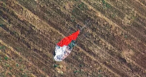 This photo taken from video provided by KABC-TV shows the parachute left by the pilot who ejected before his F-16 fighter jet crashed into a warehouse just outside March Air Reserve Base in Riverside, Calif., Thursday afternoon. (KABC-TV via AP)