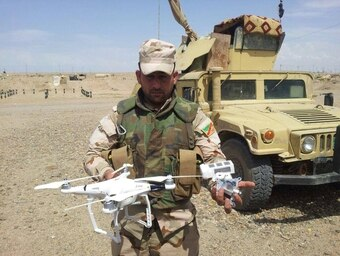 Iraqi Sgt. Hussain Musa Kathum displays an ISIS drone he shot down in Anbar province. (Iraqi Ministry of Defence)