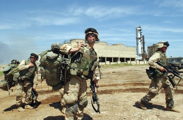 American soldiers with the 173rd Airborne division out of Vicenza, Italy, head to their vehicles as they guard an oil-gas seperation facility in the northern oil fields on the outskirts of Kirkuk, northern Iraq, Saturday April 12, 2003. (AP Photo/Peter Dejong)