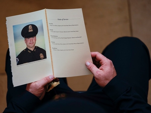 In this Feb. 3, 2021, file photo, a U.S. Capitol Police officer holds a program during a ceremony memorializing U.S. Capitol Police officer Brian Sicknick, as an urn with his cremated remains lies in honor on a black-draped table at the center of the Capitol Rotunda in Washington. The D.C. medical examiner's office says Sicknick, who was injured during the Jan. 6 insurrection, suffered a stroke and ruled the officer died from natural causes. (Demetrius Freeman/The Washington Post via AP, Pool)