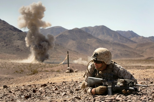 Cpl. Colton Derick, a rifleman with Bravo Company, 1st Battalion, 23rd Marine Regiment, 4th Marine Division, Marine Forces Reserve, lays down for cover during a simulated enemy explosion during the live fire company attacks during the 2015 integrated training exercise at Marine Corps Air Ground Combat Center Twentynine Palms, California, June 13, 2015. The unique terrain and weather conditions present at the range combined with the exercise simulation provide the most realistic experience of what they would go through during a deployment to Middle East.