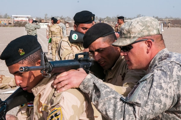 Sgt. David L. Kappel, an infantry trainer assigned to A Company, 2nd Battalion, 34th Armor Regiment, 1st Armored Brigade Combat Team, 1st Infantry Division, adjusts the rifle of an Iraqi army trainee as he instructs them how to properly