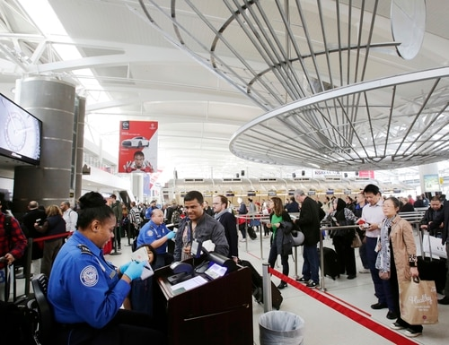 A TSA officer, left, checks a passenger's ticket, boarding pass and passport as part of security screening at John F. Kennedy International Airport in New York. (Mark Lennihan/AP)