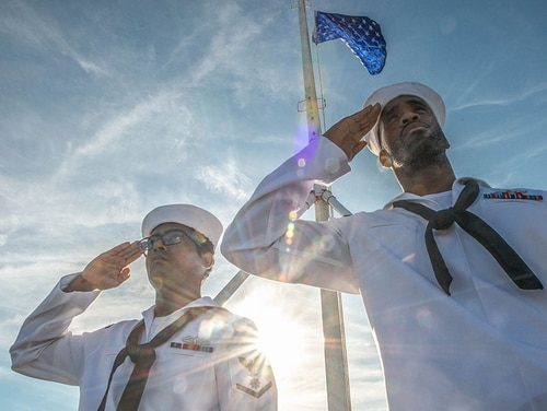 Then-Quartermaster 3rd Class Danavil Mojet, left, and then-Quartermaster 2nd Class Matthew Lewis, salute the national ensign aboard the aircraft carrier John C. Stennis after hoisting the Union Jack at morning colors in June 2019. (Staff)