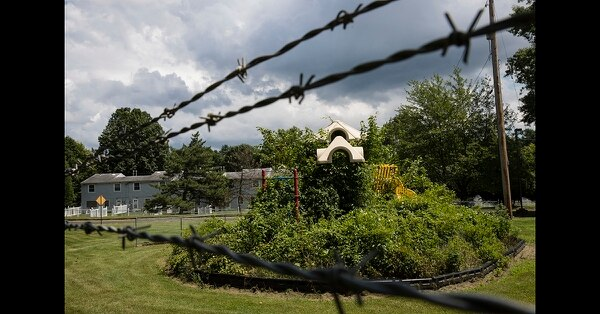 In this Aug. 1, 2018, photo weeds engulf a playground at housing section of the former Naval Air Warfare Center Warminster in Warminster, Pa. (Matt Rourke/AP)