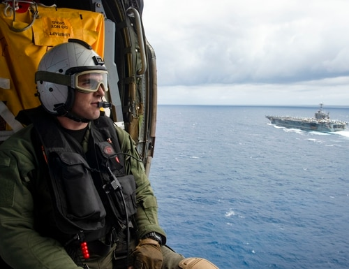 Naval Air Crewman (Helicopter) 3rd Class Jake Shelton observes the Nimitz-class aircraft carrier USS Harry S. Truman (CVN 75) in the Atlantic Ocean on May 27, 2020. (MCSN Isaac Esposito/Navy)