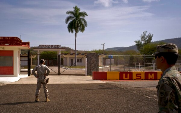 In this Wednesday, June 6, 2018, photo, reviewed by U.S. military officials, an Army soldier, right, and a Marine stand in front of the gates that separate the Cuban side from the Guantanamo Bay U.S. Naval Base. (Ramon Espinosa/AP)