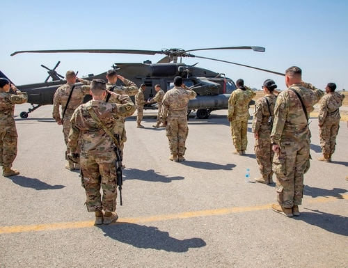 U.S. soldiers salute as the United States flag is folded at the conclusion of a reenlistment ceremony at Erbil Air Base in the Kurdistan Region of Iraq, May 22, 2020. (Spc. Angel Ruszkiewicz/Army)