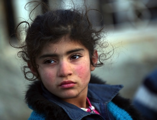 A Syrian child arrives at the Bab al-Salam border crossing with Turkey, in Syria, Saturday, Feb. 6, 2016. Thousands of Syrians have rushed toward the Turkish border, fleeing fierce Syrian government offensives and intense Russian airstrikes. Turkey has promised humanitarian help for the displaced civilians, including food and shelter, but it did not say whether it would let them cross into the country. (AP Photo/Bunyamin Aygun) TURKEY OUT