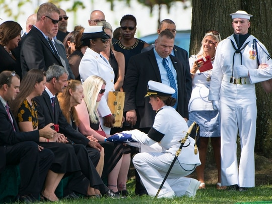 Erin Elizabeth Rehm receives the American flag from Vice Adm. Jan Tighe during a graveside service for her husband, Fire Controlman Chief Gary Leo Rehm Jr., at Arlington National Cemetery on Aug. 16, 2017. Rehm died when the guided-missile destroyer Fitzgerald collided with the Philippine-flagged merchant vessel ACX Crystal on June 17, 2017. (Elizabeth Fraser/ Arlington National Cemetery)