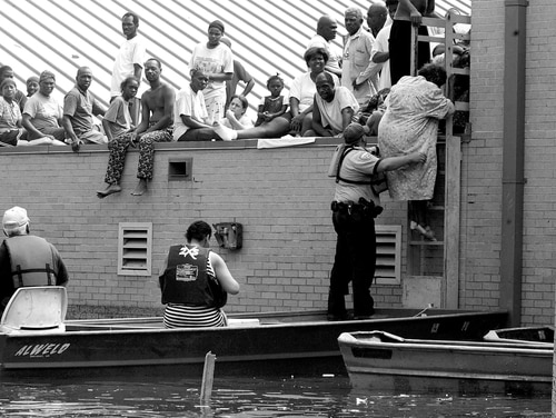NEW ORLEANS - AUGUST 30: A woman is rescued from a school rooftop after being trapped with dozens of others in high water in Orleans parish during the aftermath of Hurricane Katrina August 30, 2005 in New Orleans, Louisiana. Katrina made landfall as a Category 4 storm with sustained winds in excess of 135 mph. The school, Dr. Martin Luther King Jr. Charter School for Science and Technology in the Lower 9th Ward, closed since Katrina swept through in 2005 leaving it under 14 feet of water. The school finally re-opened August 13, 2007 to older students and on August 20 served as the first day for kindergarten and pre-K. (Photo by Mario Tama/Getty Images)