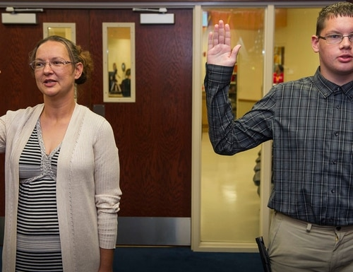 Curtis Abbott and his mother, Melissa Ensey, get sworn into the Navy at MEPS in Kansas City, Mo., on Aug. 21. (MC3 Zachary S. Eshleman/Navy)