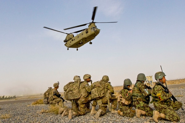 A Chinook helicopter descends over U.S. and Afghan National Army soldiers kneeling in preparation to load the helicopter for a partnered air assault mission to the town of Mirugal Kalay, on Camp Hero, Afghanistan, Oct. 23, 2014. (Sgt. 1st Class Brock Jones/Army)