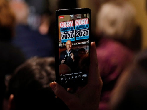 "In this Feb. 9, 2019, photo, Sen. Cory Booker, D-N.J., is seen on a cell phone as he speaks during a meet and greet with local residents in Marshalltown, Iowa. Congress is starting to show interest in prying open the ""black box"" of tech companies' artificial intelligence much the same way the federal government checks under car hoods and audits banks. One proposal introduced Wednesday, April 19, and co-sponsored by Booker, would require big companies to test the ""algorithmic accountability"" of their high-risk AI systems, such as technology that detects faces or makes important decisions based on your most sensitive personal data. (Charlie Neibergall/AP)"