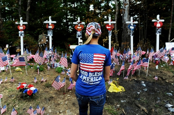 Fran Haasch inspects a memorial at the site where a crash claimed the lives of seven people riding with the Jarheads Motorcycle Club last month Saturday, July 6, 2019, in Randolph, N.H. Thousands of motorcyclists converged at the crash site at the conclusion of the 90-mile Ride for the Fallen 7 to remember the riders who were killed. (Paul Hayes/Caledonian-Record via AP)