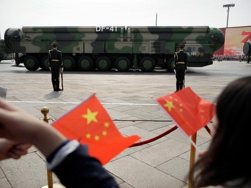 In this Oct. 1, 2019, file photo spectators wave Chinese flags as military vehicles carrying DF-41 ballistic missiles roll during a parade to commemorate the 70th anniversary of the founding of Communist China in Beijing. (Mark Schiefelbein/AP)