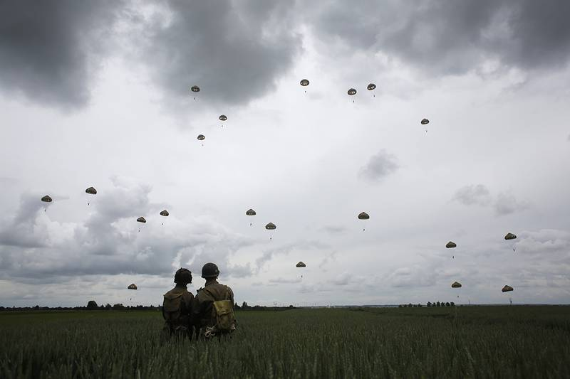WWII enthusiasts watch French and British parachutists jumping during a commemorative parachute jump over Sannerville, Normandy